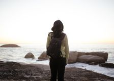 Woman Wearing White Long-sleeved Top and Black Pants Carrying Black Backpack While Standing on Shore during Adytime royalty free stock photo
