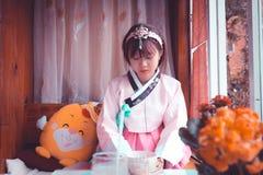 Woman Wearing White and Pink Traditional Korean Dress Sitting Near Yellow Plush Toy Stock Image