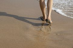 Woman wearing white sandals walking on sand beach royalty free stock photography