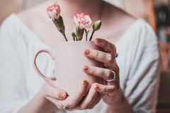 Woman Wearing White Shirt Holding Pink Mug With White Petaled Flowers stock photos