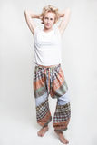 Woman in white shirt and pants. A woman wearing a white shirt and large pajama pants stock photo