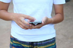 Woman wearing a white shirt playing mobile. Royalty Free Stock Photos