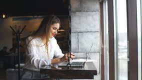 Woman wearing white shirt smile and thinking in Coffee shop cafe with computer laptop on the table. Smiling businesswoman typing on her laptop and uses a stock video footage