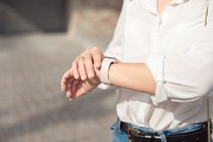 Woman wearing white shirt wearing blue jeans and a gentle nude manicure looks at the watch close-up. royalty free stock photo