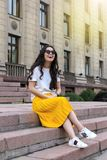 Woman Wearing White Shirt and Yellow Skirt Sitting on Brown Concrete Brick Stairs Royalty Free Stock Photos