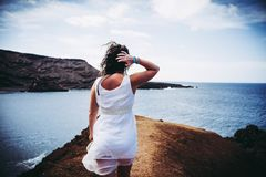 Woman Wearing White Sleeveless Mini Dress on Top of Brown Sand Near Body of Water stock image