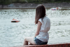Woman Wearing a White Sleeveless Shirt Sitting Near a Body of Water Stock Images