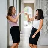 Woman Wearing White Sleeveless Top and Black Pencil Skirt Facing Woman Wearing Pink Sleeveless Top and Black Pencil Skirt Leaning stock image