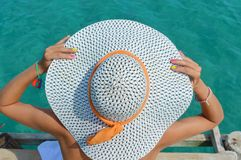 Woman wearing a white straw hat looking at the water Royalty Free Stock Images