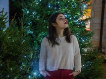 Woman Wearing White Sweater With Red Skirt Near Green Christmas Tree stock photo