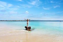 Woman wearing white swimsuit at idyllic beach feeling good stock photos