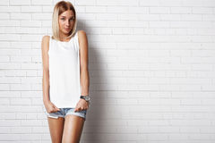 Woman wearing white t-shirt. Against brick wall Stock Images