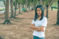 Woman wearing white t-shirt, she standing on green grass in the park and smiling. Woman wearing white t-shirt, she standing on green grass and smiling at public Royalty Free Stock Image