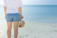 Woman wearing white t-shirt, she standing on sand beach and holding weave hat in hand, she looking at the sea and blue sky. Selective focus Stock Image