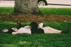Woman Wearing White Tank Top Lying On Green Grass stock photos