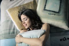 Woman Wearing White Tank-top Sleeping on Gray and White Bedspread Stock Image