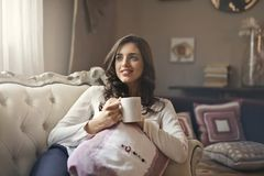 Woman Wearing White Top Drinking Beverage from White Ceramic Mug While Lying on Sofa Inside Well Lit Room Stock Photography