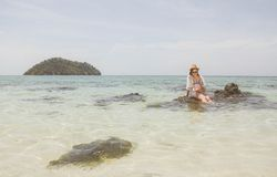 Woman Wearing White Top Sitting on Brown Rock on Body of Water during Stock Image