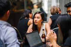 Woman Wearing White Top Sitting Near Table With People stock images
