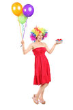 Woman wearing a wig and holding present and balloons Royalty Free Stock Photography