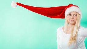 Woman wearing windblown long Santa hat Royalty Free Stock Image