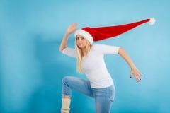 Woman wearing windblown long Santa hat Royalty Free Stock Images