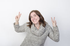 Woman is wearing winter clothes and makes victory gesture. Royalty Free Stock Photography