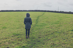 Woman wearing winter coat walking in field Stock Photography