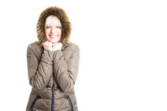 Woman wearing winter jacket with hood being cold and smiling Royalty Free Stock Image