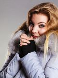 Woman wearing winter warm furry jacket. Seasonal fashion, clothes and clothing concept. Woman wearing light winter warm furry coat feeling very cold, warming Stock Photos