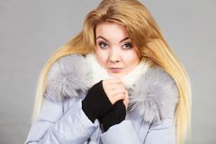 Woman wearing winter warm furry jacket. Seasonal fashion, clothes and clothing concept. Woman wearing light winter warm furry coat feeling very cold, warming stock photography