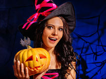 Woman wearing witch hat holding big pumpkin. Royalty Free Stock Photos