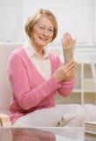 Woman wearing wrist stabilizer bandage on arm. Senior woman wearing wrist stabilizer bandage on arm Stock Photo