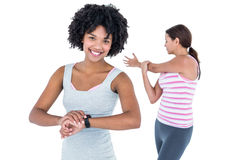 Woman wearing wristwatch while female friend exercising Royalty Free Stock Photography