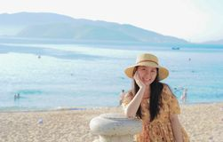 Woman Wearing Yellow Floral Dress and Sun Hat on Beach Stock Photography