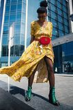 Woman Wearing Yellow Floral V-neck Long Dress and Pair of Green Wedge Sandals stock photo