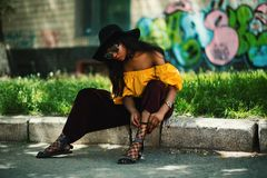 Woman Wearing Yellow Off-shoulder Top and Black Pants Sitting on Sidewalk Fixing Lace Sandals royalty free stock photo