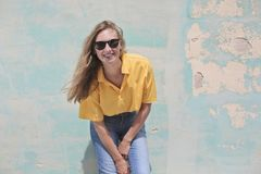 Woman Wearing Yellow Polo Shirt Standing in Front of Teal Concrete Wall Stock Image