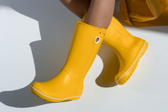 Woman wearing yellow rubber boots sitting on floor Stock Images