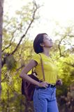 Woman Wearing Yellow Shirt and Looking Up Surrounded by Trees Stock Photo