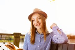 Woman Wears Black and White Striped Top Leaning on Brown Rail stock image