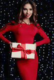 Woman wears elegant dress and bijou, holding present with red bow Royalty Free Stock Photos