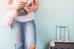 Woman wears jeans and t-shirt with camera and passport using mob Stock Photos