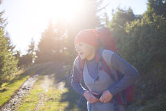 A woman wears a large backpack. A young girl wearing a large backpack for Hiking in the mountains Royalty Free Stock Images