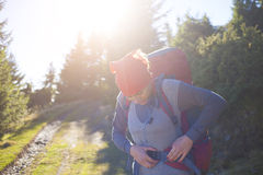 A woman wears a large backpack. A young girl wearing a large backpack for Hiking in the mountains Stock Photos