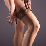 The woman wears a nylon stocking on slender leg. Nude female legs, slender legs, puts a nylon stocking, square image, smooth skin, white background, healthy skin Stock Photos