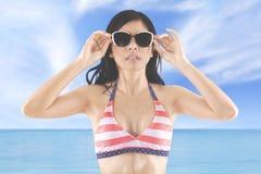 Woman wears sunglasses and striped bikini Royalty Free Stock Image