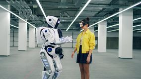Woman wears VR glasses while a droid touches her hand. stock footage