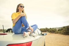 Woman Wears Yellow Shirt and Blue Denim Jeans Sits on Silver Car Royalty Free Stock Photos