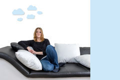 Woman weather forecast concept. Grinning long haired young woman is sitting on a black and white couch with black and white pillows. Woman is looking upwards on Royalty Free Stock Photo